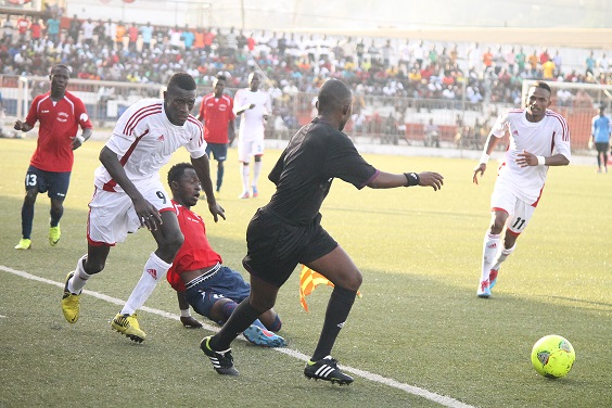 A Liberian  (In red) and a Gambian tussle for the ball in this action from Sunday's match