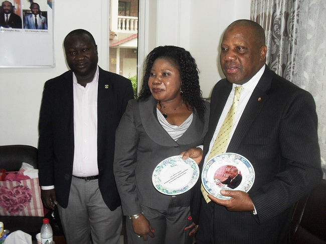 Amb. Kamara displays souvenirs presented to him by the embassy. On his right are secretary Nyangbe and charge d' affairs Barchue