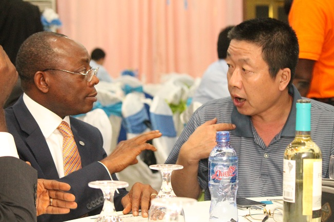 Ecobank Liberia Managing Director Adeleke (left) chats with a Chinese businessman
