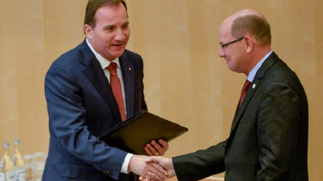 Newly-elected premier Stefan Löfven (left) shakes hands with Speaker of the Parliament Urban Ahlin.
