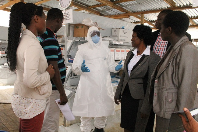 An Ebola survivor, now a health worker, talks with about his work at the center