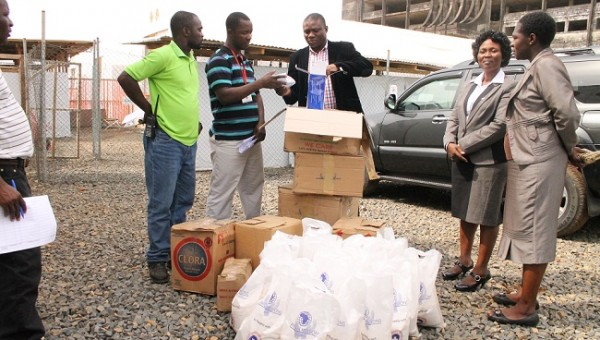 Pastor Olugbenga (black coat) presents the items