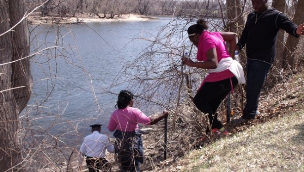Volunteers assist one another in climbing down a terrible slop along the Mississippi