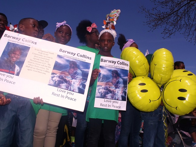 Kids hold Barway posters and toys at Saturday's memoral in Crystal