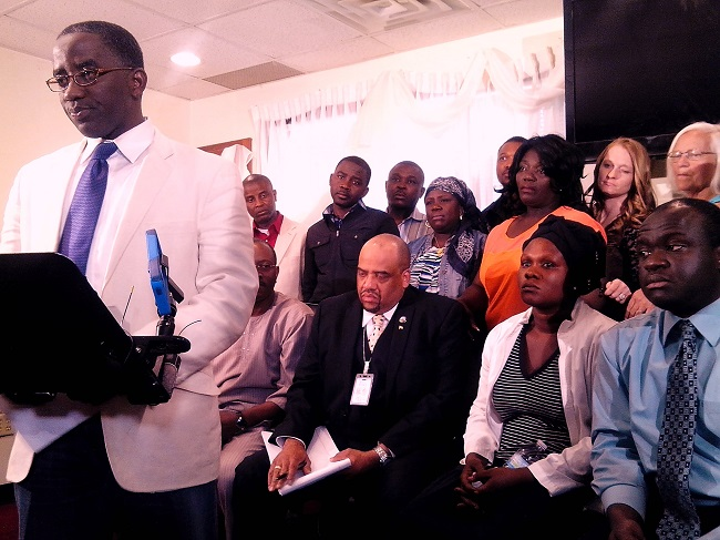 Seyon Nyanwleh welcomes the press as Pastor Collins, Louise and City Commissioner David Singleton (seated) look on