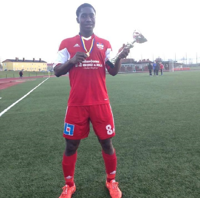 Lansana happily displays the trophy and medal