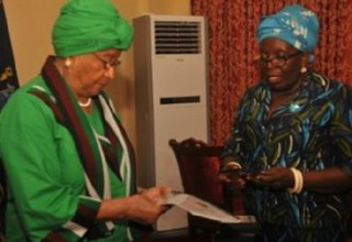 Cllr. Scott (right)  presents NCC report and CDs of the 1986 Constitution in the vernaculars to President Sirleaf