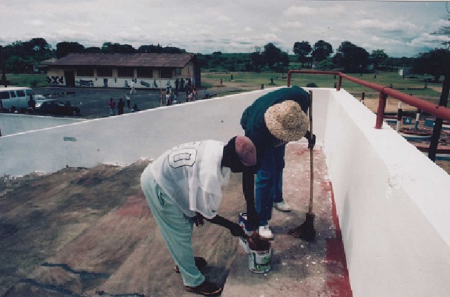 Former Taylor's Information Minister Joe Wolobah Mulbah and an assistant help with Kendeja's renovation exercise in 1996-97. In the picture is the center's mini stadium plus the arts building in background. Photo James Fasuekoi