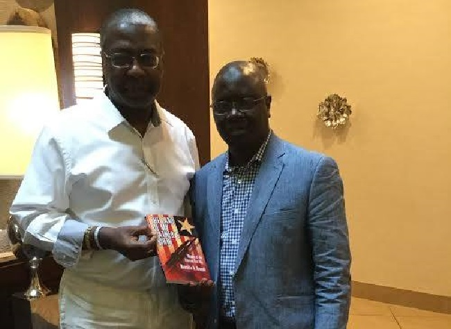 Konneh ( right), the writer of this piece, presents a copy of his book to Dr. J. Mills Jones